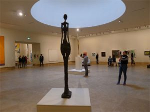 • TALL FIGURE IV by Alberto Giacometti and BIRD IN SPACE by Constantin Brancusi dominate large gallery with domed ceiling at the Norton Simon Museum.